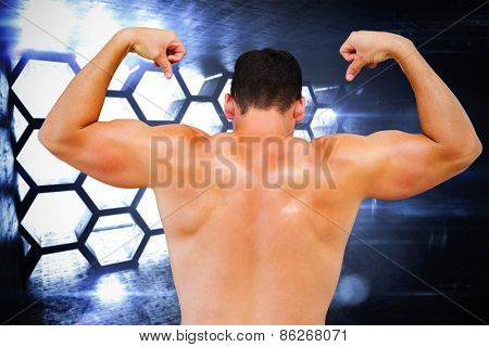 Attractive bodybuilder against hexagon room