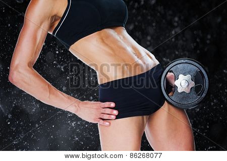 Female bodybuilder holding large black dumbbell mid section against black background