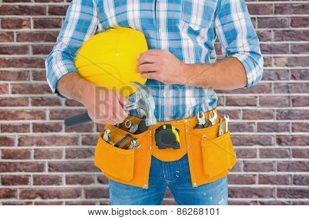 Manual worker wearing tool belt while holding hammer and helmet against red brick wall