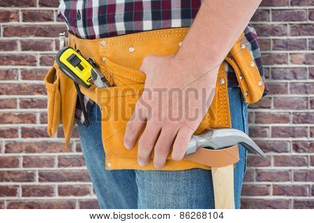 Close-up of male repairman wearing tool belt against red brick wall
