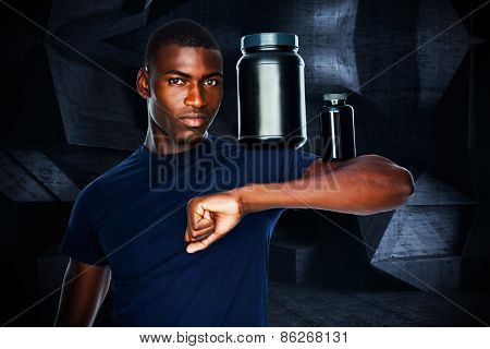 Fit man holding bottles with supplements on his biceps against dark room