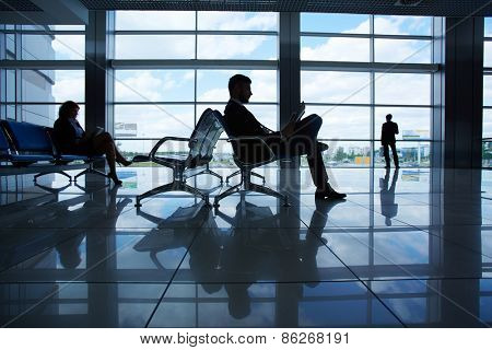 Outline of businessman reading while waiting for departure in airport