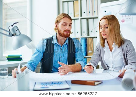 Two engineers examining blueprint