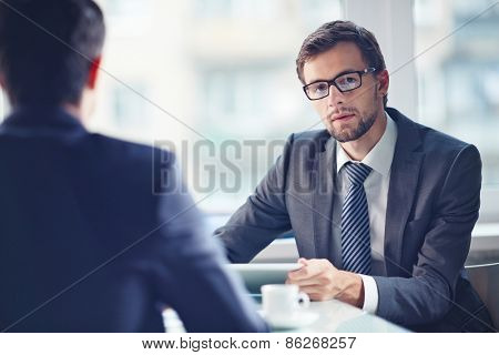 Serious businessman looking at camera at workplace with his colleague near by