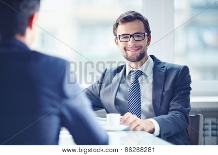Smiling businessman looking at camera during coffee break with his colleague