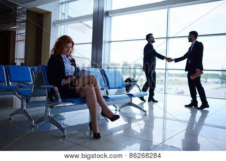 Young woman using touchpad while waiting for departure on background of two men greeting one another