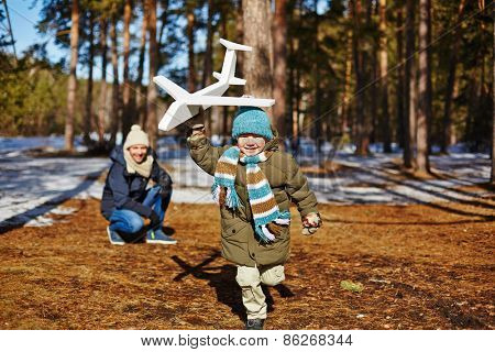 Little boy running with toy plane and his father looking at him