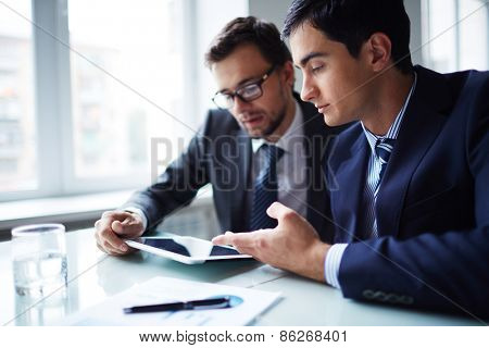 Two businessmen working with touchpad at meeting in office