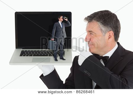 Businessman looking through binoculars against waiter pointing to laptop
