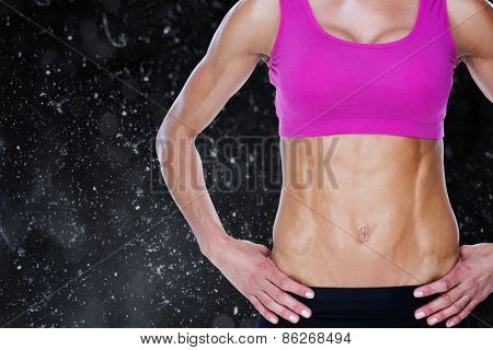 Female bodybuilder posing with hands on hips mid section against black background