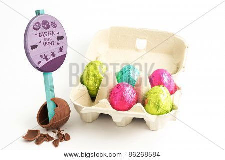 Easter egg hunt sign against carton of easter eggs with one broken on surface