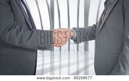 Close up on two businesspeople shaking hands against white room with large window overlooking city