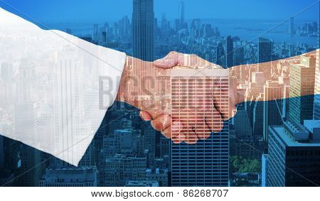 Extreme closeup of a doctor and patient shaking hands against city skyline