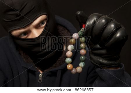 Thief. Man in black mask with a jade necklace. Focus on necklace
