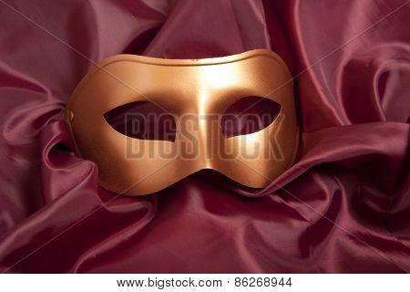 Golden carnival mask on red satin background