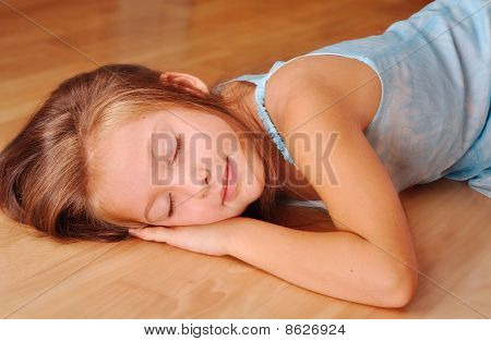Girl In A Blue Sleeping, Lying On The Floor