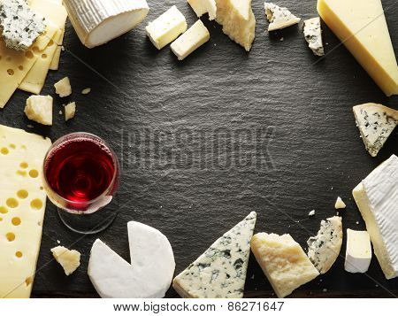 Different types of cheeses with wine glass. Top view.