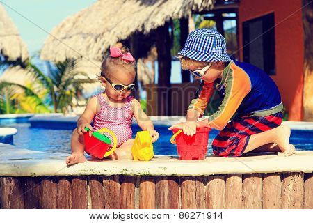 little boy and toddler girl playing in swimming pool