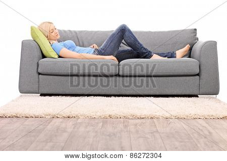 Studio shot of a young blond woman taking a nap on a sofa isolated on white background