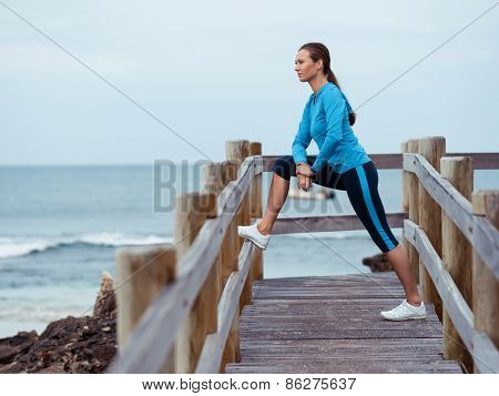 Sporty young woman stretching next to the sea coast