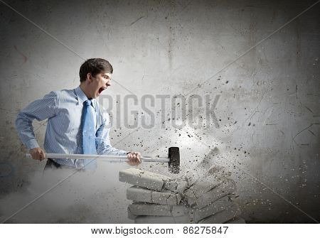 Young angry businessman crashing bricks with hammer