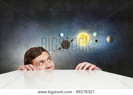 Young businessman looking from under table and planets of space spinning around