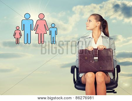 Business woman in skirt, blouse and jacket, sitting on chair, holding briefcase imagines family. Aga