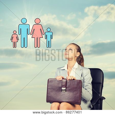 Business woman in skirt, blouse and jacket, sitting on chair imagines family. Against background of