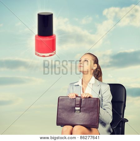 Business woman in skirt, blouse and jacket, sitting on chair imagines nail polish. Against backgroun