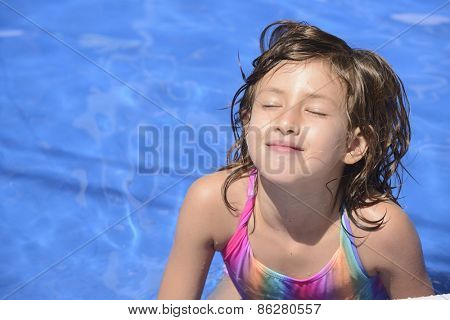 Happy little girl in outdoor sunny day swimming in the pool.
