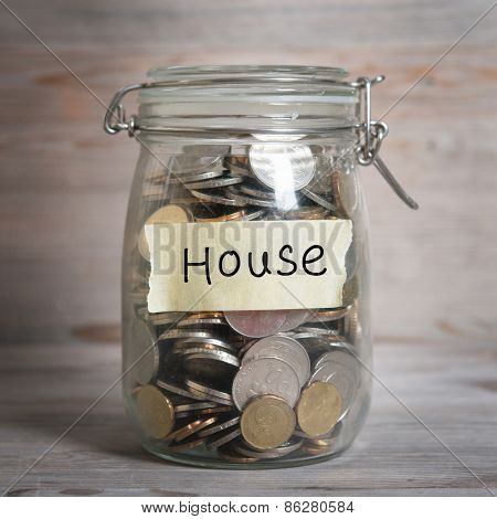 Coins in glass jar with house label, financial concept. Vintage wooden background with dramatic light.