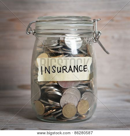 Coins in glass jar with insurance label, financial concept. Vintage wooden background with dramatic light.