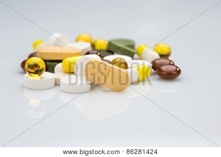 Pile of various colorful pills isolated on white