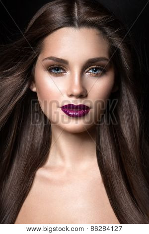 Beautiful girl with golden makeup and burgundy lips with the wind in hair. Beauty face.
