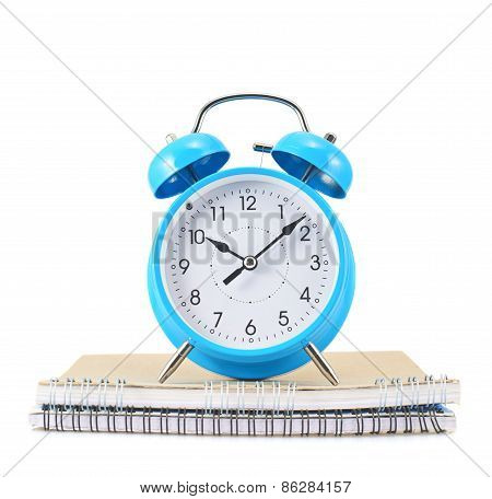 Blue alarm clock over the notebook