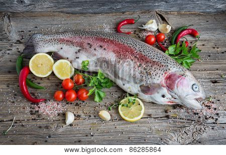Raw Trout Fish On Wooden Background With Lemon, Tomato, Red Chili Pepper, Garlic And Peppercorns