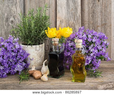 Olive Oil And Vinegar In Bottles On Wooden Table With Garlic And Rosemary In Flowerpot
