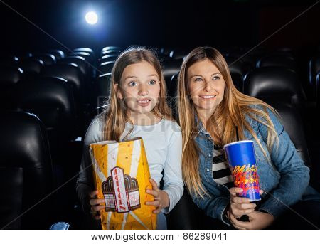 Surprised mother and daughter watching film in movie theater