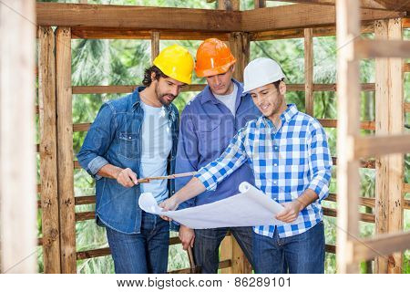 Male architects discussing over blueprint in wooden cabin at site