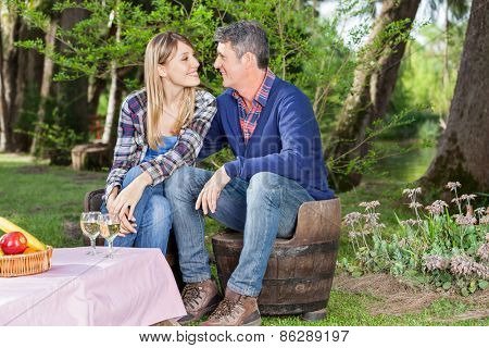 Smiling couple looking at each other while sitting on chairs at campsite