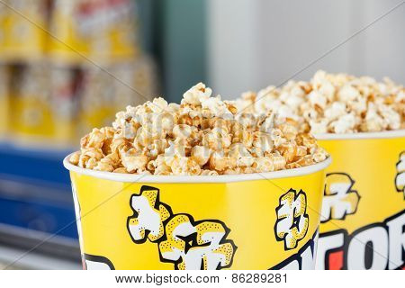 Closeup of roasted popcorns filled in buckets at cinema