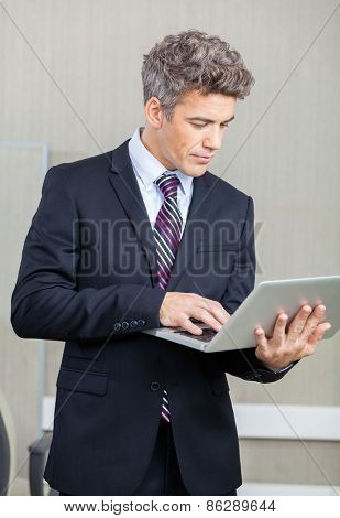 Mid adult businessman using laptop at call center