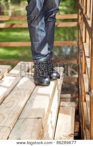Low section of male construction worker standing on stacked wooden planks at site