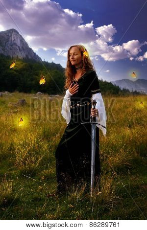 Mystical Woman With A Sword And Historic Dress On A  Mountain Meadow With Yellow Butterflies