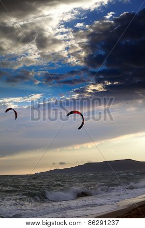 Two Silhouette Of Power Kites At Sunset Sky