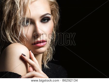 Beautiful blond girl with wet hair, dark makeup and pale lips. Beauty face.