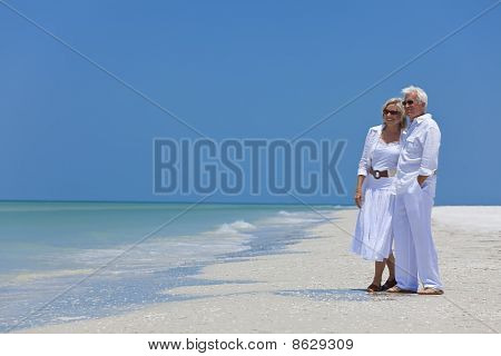 Feliz pareja Senior, mirando al mar en una playa Tropical