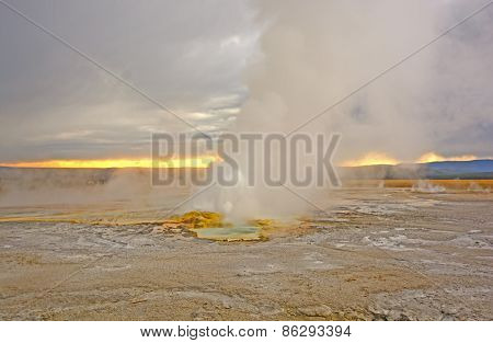 Geyser Erupting At Sunset