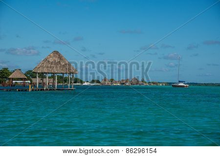 Caribbean Scene With Hut And Sailboat. Bacalar, Near Tulum. Traveling Mexico.