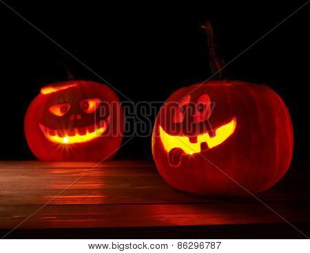 Two glowing jack o lantern pumpkins